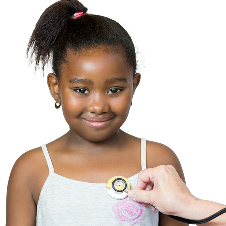Close up portrait of cute little african girl having heartbeat taken.Hand positioning stethoscope against chest.Isolated on white background.