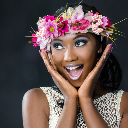 Close up fun portrait of attractive young african bride wearing colorful flower garland.Girl pulling funny face with hands next to face looking at corner.