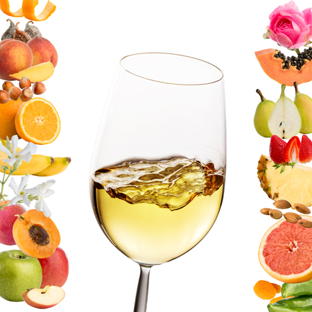Extreme close up of glass with white wine.Conceptual  fruit and flower aromas around glass.Isolated on white background.