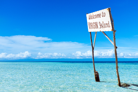 Tropical island with big white billboard in middle of lagoon.Advertisement with copy space on wooden poles in shallow transparent blue water. Stock Photo