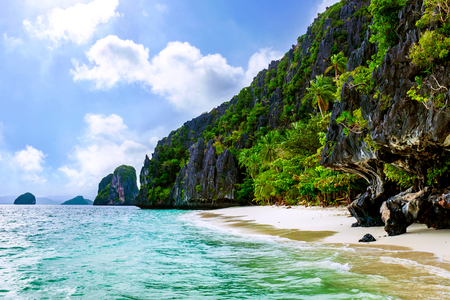 Idyllic paradise beach with tropical green vegetation and mountains in background. Stock Photo