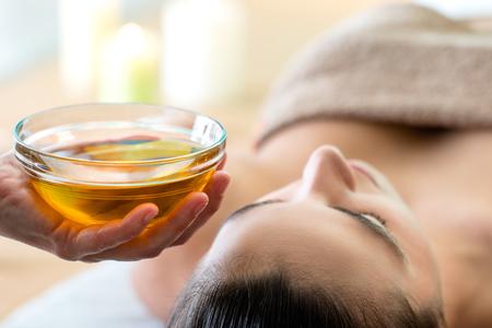 Gros plan macro de main tenant un bol en verre avec de l'huile aromatique à côté de la tête de la femme dans le spa.
