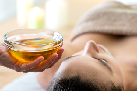 Macro close up of hand holding glass bowl with aromatic oil next to woman's head in spa. Stockfoto
