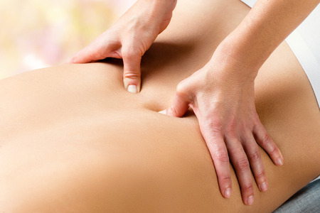 Close up detail of hands applying pressure with thumbs on lower lumbar area on woman. Stock Photo