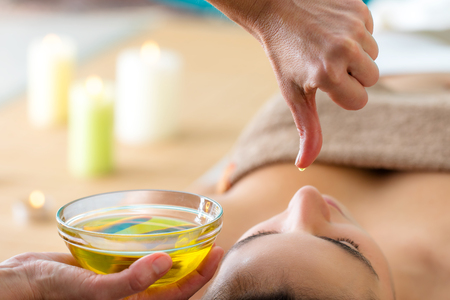 Macro close up of hand with oil drop above woman's head in spa. Aromatic oil in glass bowl next to woman at Ayurvedic massage.