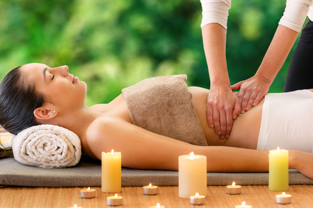 Close up portrait of woman enjoying curative Ayurvedic massage against green nature background. Therapist massaging belly.