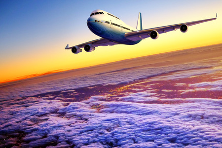 Commercial airbus flying above clouds and city at dawn.Front and side view of aircraft in flight against sunset skyline. Editorial
