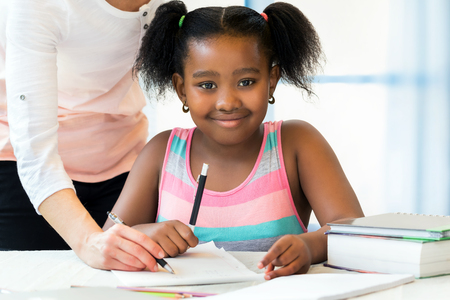 Close up portrait of cute little african student doing homework with caucasian teacher. Ponytailed girl sitting at desk with pen,paper and books.