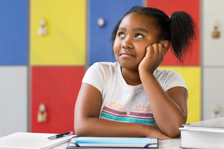 Close up portrait of little african female student sitting at desk in classroom. Tedious kid with bored wondering facial expression staring and looking up. Stock Photo