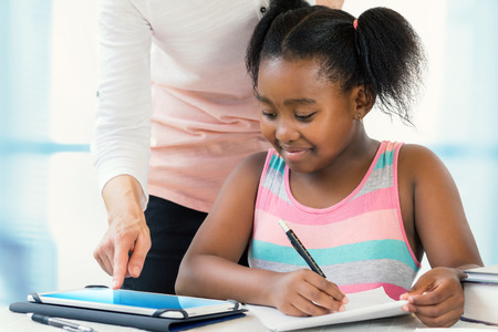 Close up portrait of little african girl struggling with school work.Caucasian teacher showing results on digital tablet at desk. Zdjęcie Seryjne