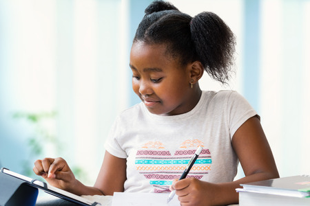 Close up portrait of cute little african girl doing home work at desk. Ponytailed kid typing on digital tablet and writing with pen on paper. Imagens