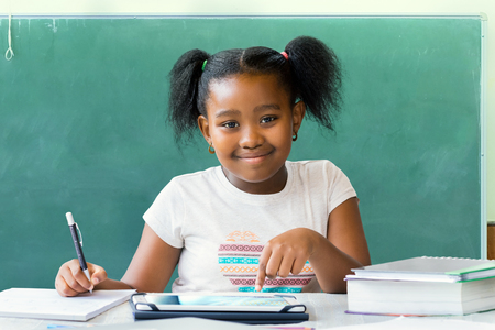 Close up portrait of cute little african student writing and working at desk with digital tablet. Ponytailed kid smiling with blank black board in background. Imagens