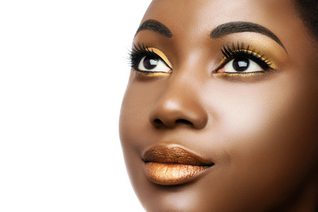 Macro close up cosmetic beauty portrait of young black woman.Girl wearing professional make up isolated on white background.