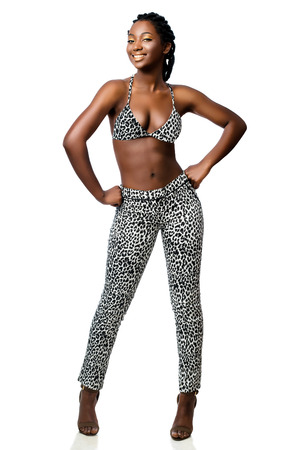 Full length portrait of attractive african woman wearing leopard pants and bikini top standing with hand on hips.Smiling girl with braided hairstyle isolated on white background. Zdjęcie Seryjne