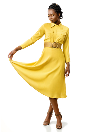 Full length portrait of attractive young african american girl in stylish yellow dress. Elegant woman holding end of dress with eyes closed.Isolated on white background. 스톡 콘텐츠