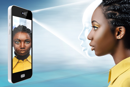 Smart phone projecting light bean on african female face.Side view of conceptual face recognition technology.