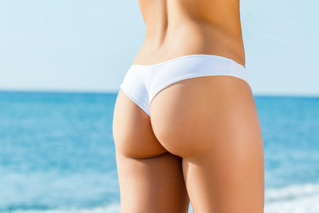 Close up detail of female buttock in white bikini outdoors. Rear view of slim woman with tanned skin tone. 免版税图像 - 108765776