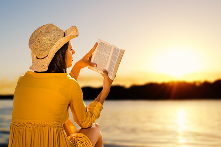 Young woman wearing hat next to river reading a book. Side view of Girl in yellow dress against sunset background.