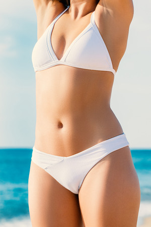 Close up detail of female torso in white bikini outdoors.Slim muscular body with healthy skin tone. Zdjęcie Seryjne