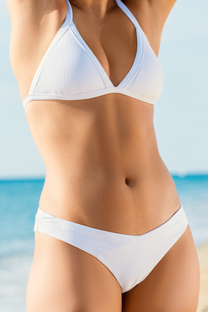 Close up detail of sporty female torso in white bikini outdoors. Muscular body with healthy skin and flat tummy.