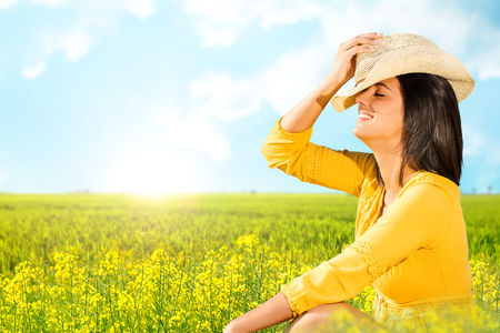 Close up portrait of attractive young woman in yellow dress sitting in green flower field.Happy girl wearing hat smiling with eyes closed enjoying nature.