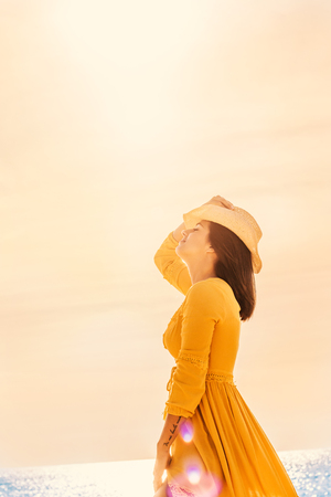 Close up portrait of young carefree woman in yellow dress at sunset. Girl wearing hat with eyes closed.