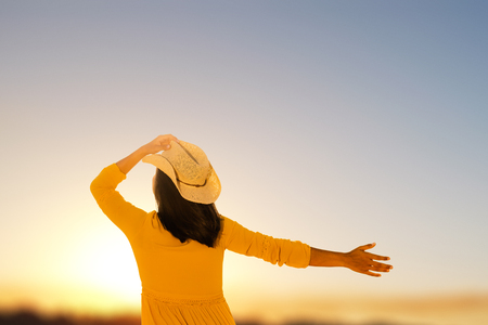 Close up rear view of young woman in yellow dress looking at sunset. Girl holding hat on head with one hand and raising other hand in sky.