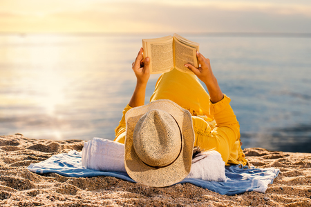 Close up of woman in yellow dress laying on beach reading a book. Rear view of woman wearing hat against idyllic sunset.