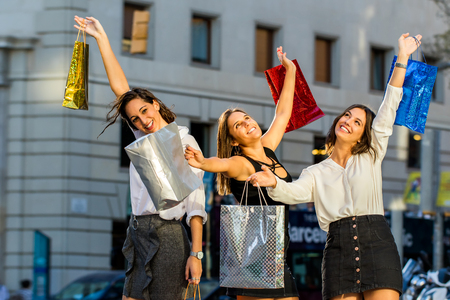 Close up portrait of three young attractive girls raising hands with shopping bags. Happy female hipsters raising hands in city.