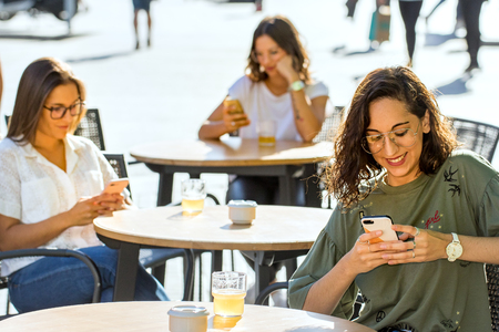 Close up portrait of three young female students sitting with smartphones on terrace in city. Conceptual addiction behaviour among young adults. Zdjęcie Seryjne