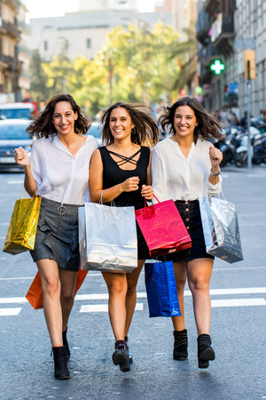 Full length action portrait of three attractive girlfriends walking together with shopping bags. Young women dressed up in skirts crossing the street with out of focus busy traffic in background.
