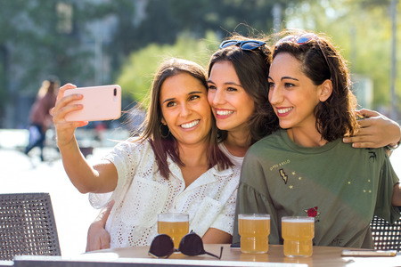 Close up portrait of  three girlfriends taking selfie photo on terrace. Young attractive women in city posing together at smartphone. Zdjęcie Seryjne