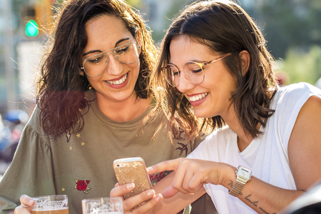 Close up portrait of two girlfriends socialising together on smartphone.Young students outdoors on city terrace.