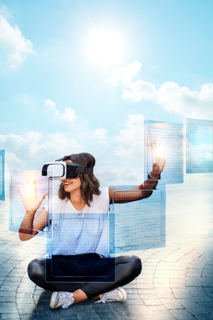 Conceptual portrait of young woman wearing virtual reality glasses. Vertical shot of girl sitting and touching transparent data screens.