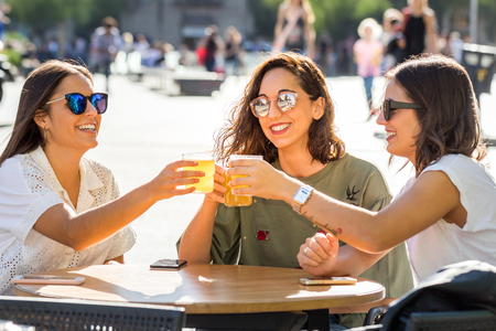Close up portrait of three happy girlfriends making a toast with drinks. Young women sitting on terrace in city with out of focus crowd in background.