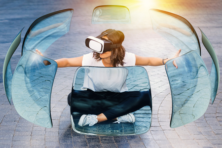 Conceptual portrait of young woman wearing virtual reality glasses. Girl sitting on stone floor touching transparent glass panels surrounding her.