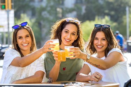 Close up portrait of three girlfriends having a drink together on urban terrace. Young women looking at camera making a toast. Zdjęcie Seryjne