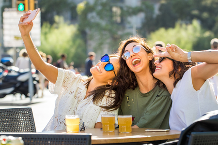 Close up fun snapshot portrait of three girlfriends posing together at camera. Young university students having a drink together on terrace in city. One girl taking selfie with smartphone.
