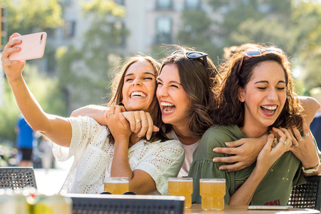 Close up fun portrait of three happy girlfriends taking selfie together on terrace. Young attractive women in city posing at smartphone. Zdjęcie Seryjne