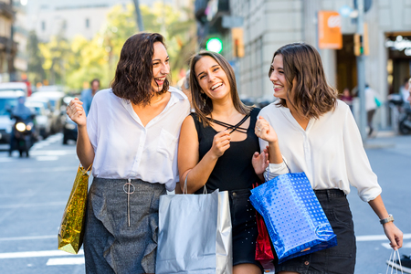 Close up action shot of three young girlfriends walking together with shopping bags.Laughing young women dressed up in skirts crossing the street with out of focus busy traffic in background.