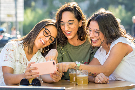 Close up portrait of three happy girlfriends looking together at smartphone. Young female students sitting on terrace in city with drinks.