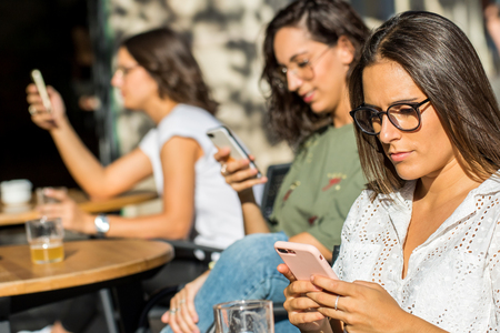 Close up portrait of three young female women busy on smartphones. Girls sitting on city terrace interacting on individual phones.
