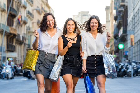 Close up portrait of three attractive young girls walking with shopping bags in city.Laughing young women dressed up in skirts crossing the street with out of focus busy traffic in background.