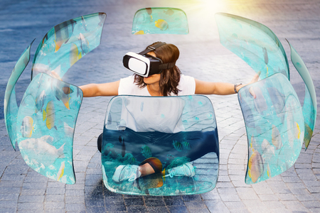 Conceptual portrait of young girl wearing virtual reality glasses. Woman touching  transparent glass panels with projected underwater aquarium scene.