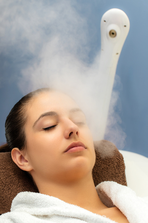 Close up portrait of young woman having thermal steam treatment in spa. Girl with eyes closed in white gown laying on couch. 写真素材