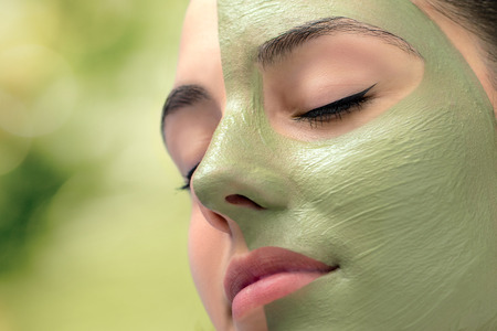 Macro close up head shot of attractive woman with green algae facial mask in spa. Stock Photo