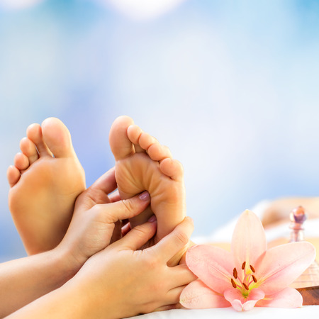 Close up foot reflexology. Podiatrist massaging female foot against colourful background.