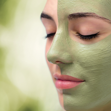 Macro  close up portrait of facial green algae cleansing mask on young woman.
