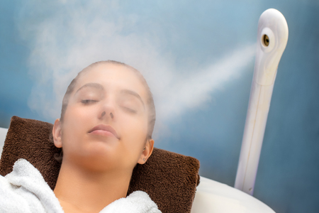 Close up portrait of young woman with eyes closed having thermal steam treatment on face. Girl wearing white gown laying on couch in spa.