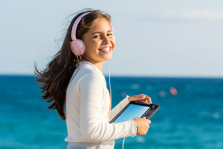 Close up outdoor portrait handsome tween girl with headphones. Girl holding digital tablet with blank screen against sea and sky background.